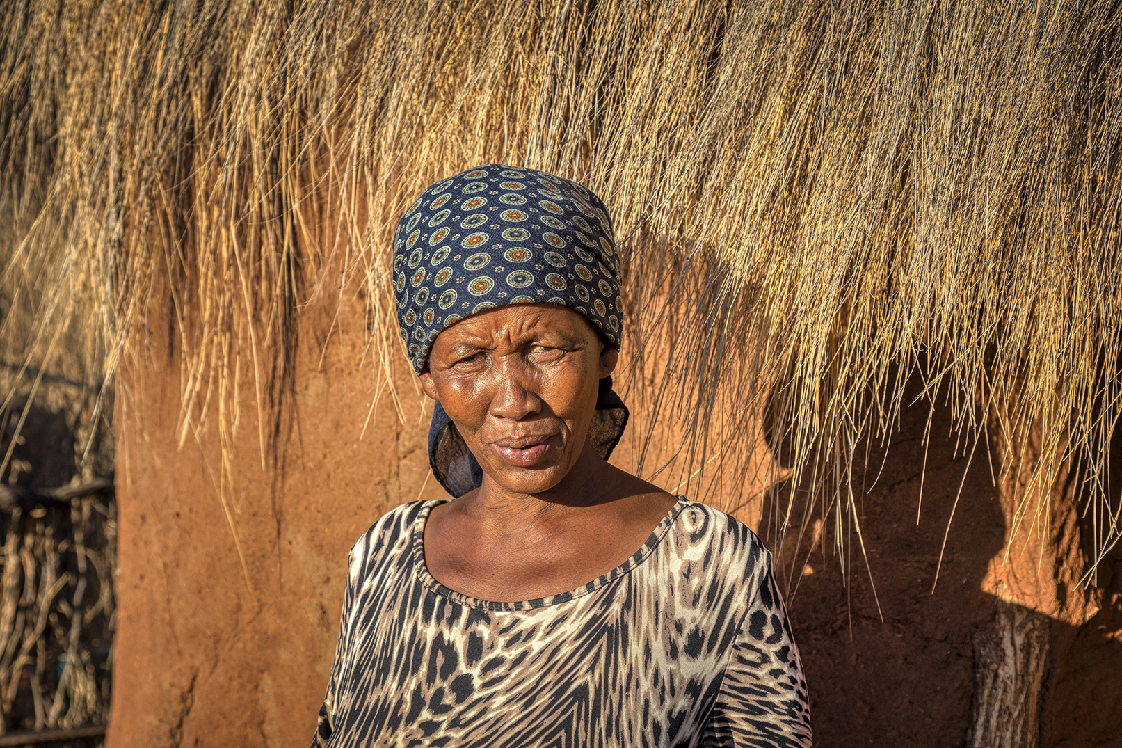 Old African woman in front of her house, village in Botswana
