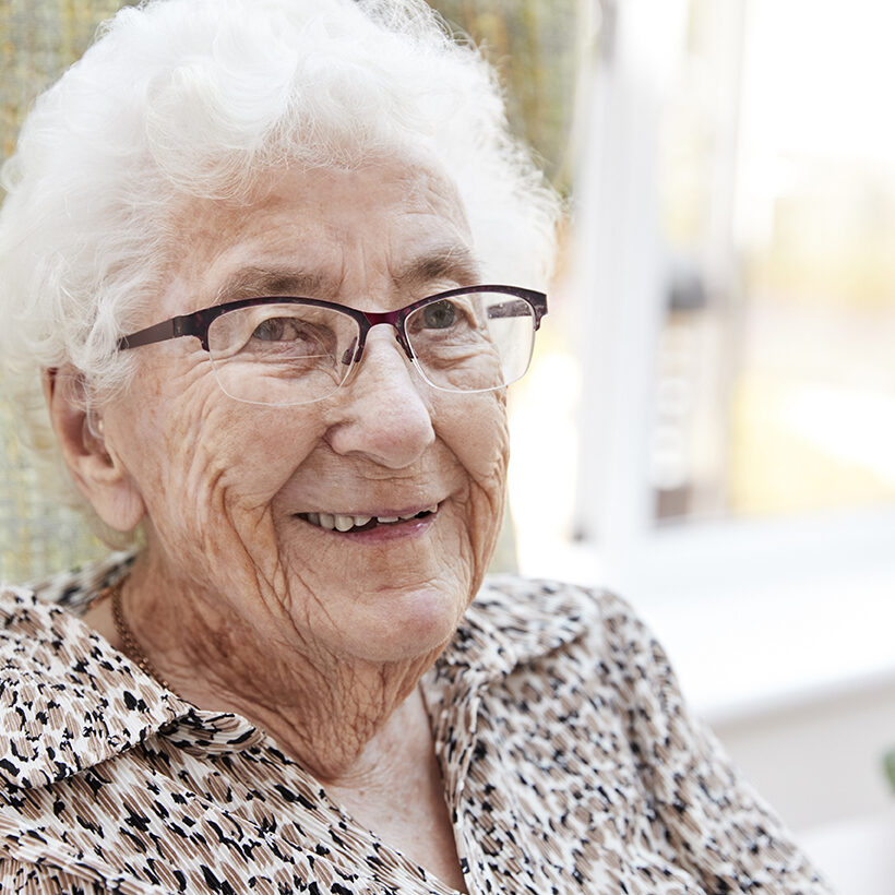 Portrait Of Senior Woman Sitting In Chair In Lounge Of Retirement Home